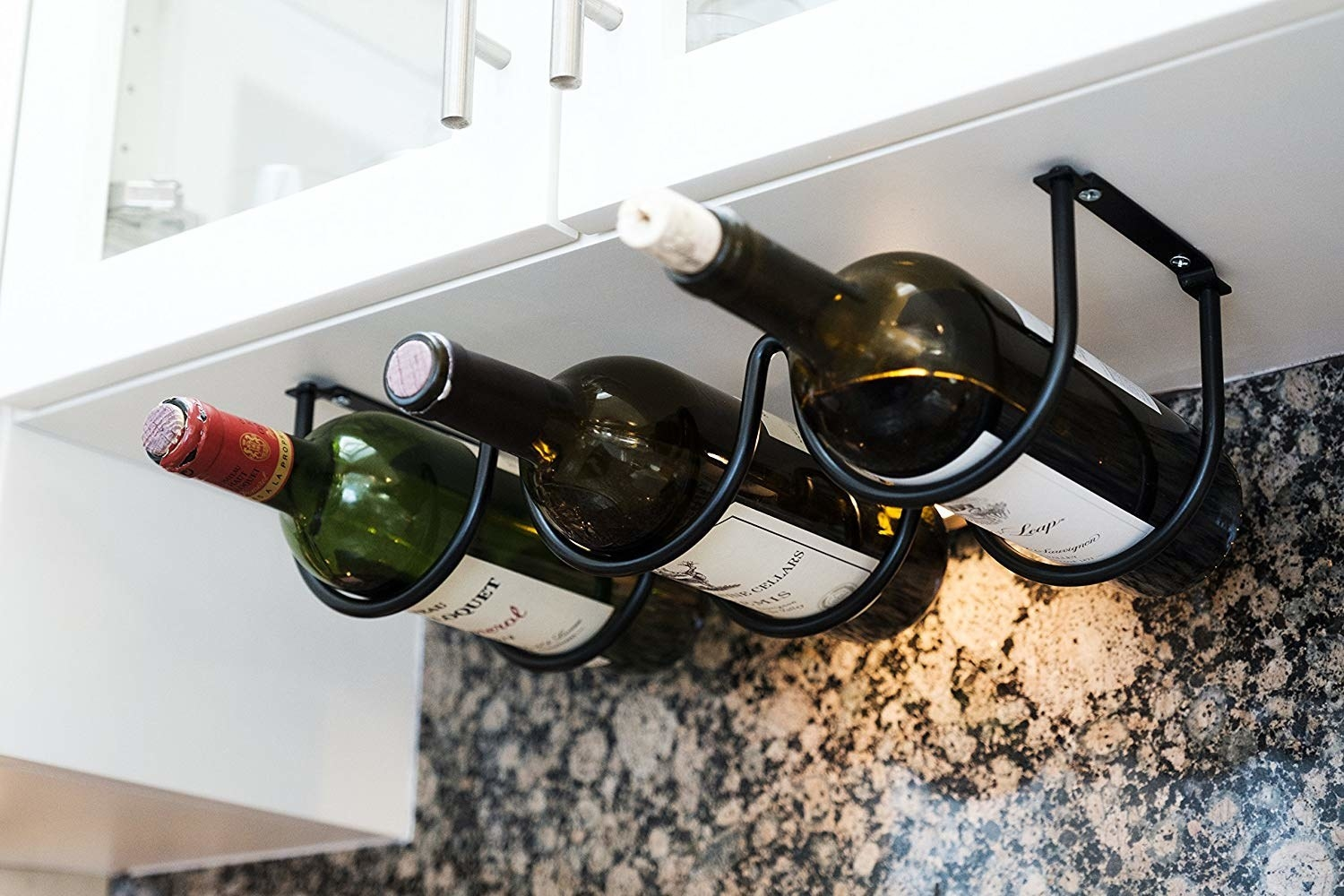 A three-bottle wine rack installed on the underside of a kitchen cabinet