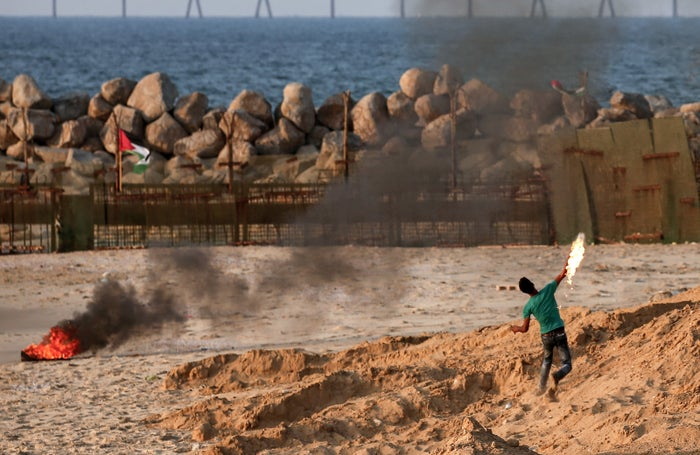 A Palestinian man throws a Molotov cocktail along the Gaza sea barrier.