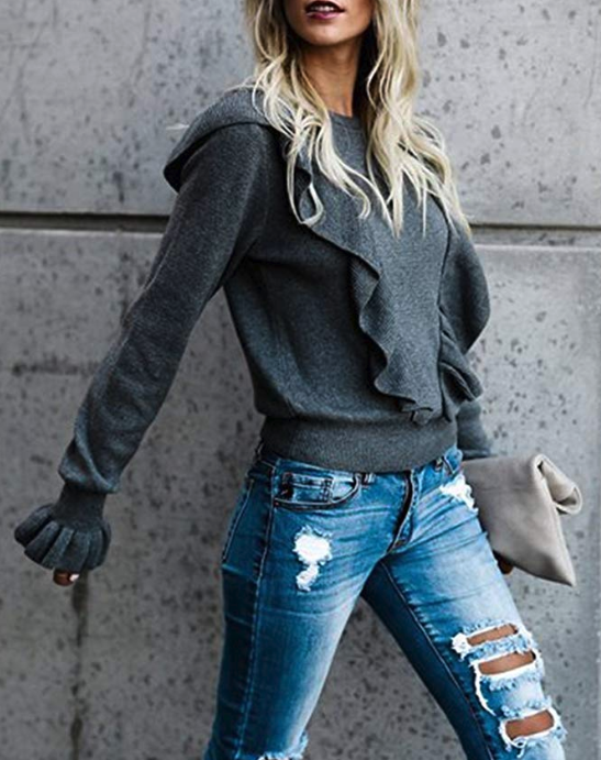 Model wearing the crew-neck shirt in dark grey with two ruffles over the shoulders forming a v on the front and ruffles on the ends of the sleeves.