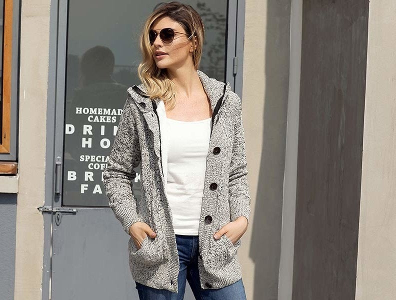 Model wearing the sweater in grey open, showing a tiny bit of the white fleece inside. It has also pockets, a hood, and big black buttons on the left side.