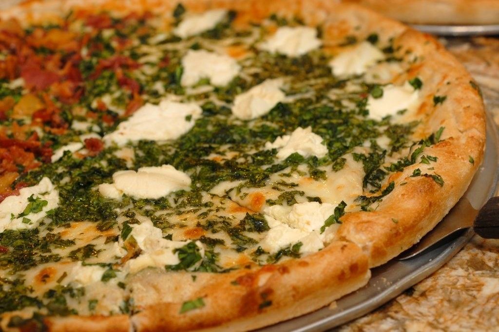 """Signature slice: """"Margarita Fire & Stone,"""" topped with tomatoes, ricotta, and basil pesto."""