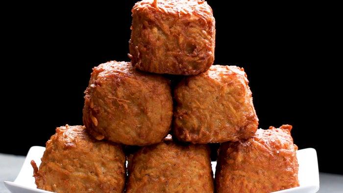 4 porçõesVocê vai precisar de: 15 fatias de queijo cheddar15 fatias de presunto6 batatas médias ou 3 grandes1 ½ colheres de chá de sal½ colher de chá de pimenta¼ de xícara de farinha de trigo (30g)1 ovoóleo para fritarModo de preparo: Em uma tábua de corte, coloque uma fatia do queijo cheddar e coloque uma do presunto por cima. Caso o presunto não for quadrado, corte-o para ficar do mesmo tamanho da fatia do queijo. Misture os retalhos do presunto com a cebola, a pimenta e o ovo. Corte o presunto e o queijo em 4 quadrados iguais. Repita com o restante do presunto e do queijo.Empilhe o presunto e o queijo até ter 10 camadas de presunto e 10 de queijo.Em uma tábua de corte, descasque as batatas. Rale as batatas em uma tigela grande forrada com um pano de prato.Assim que todas as batatas forem raladas, enrole a toalha firmemente e torça-a, espremendo toda a água das batatas. Descarte a água das batatas.Coloque as batatas raladas em uma tigela limpa e acrescente 1 colher de chá de sal, pimenta, farinha e o ovo. Misture bem.Envolva o cubo de presunto e queijo com a mistura de batata. Achate cada lado para criar um cubo. Repita com o resto dos cubos.Em uma assadeira forrada com papel-manteiga, coloque os cubos de batata suíça. Leve ao congelador por 2-3 horas ou até ficarem sólidos.Aqueça 10 cm de óleo em uma panela grande até a temperatura chegar aos 180ºC.Frite cada cubo por 4 minutos até dourar. Coloque-os sobre uma grade de esfriamento ou deixe-os secar sobre toalhas de papel. Deixe esfriar por 5 minutos. Polvilhe com o resto do sal.Sirva imediatamente.Bom apetite!