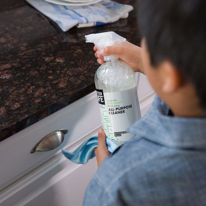A model spraying the cleaner on a granite countertop