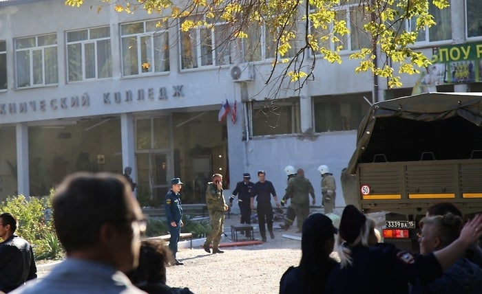 Russian Emergency Situations Ministry workers and police officers walk outside a college building in Kerch, Crimea, in Russia.