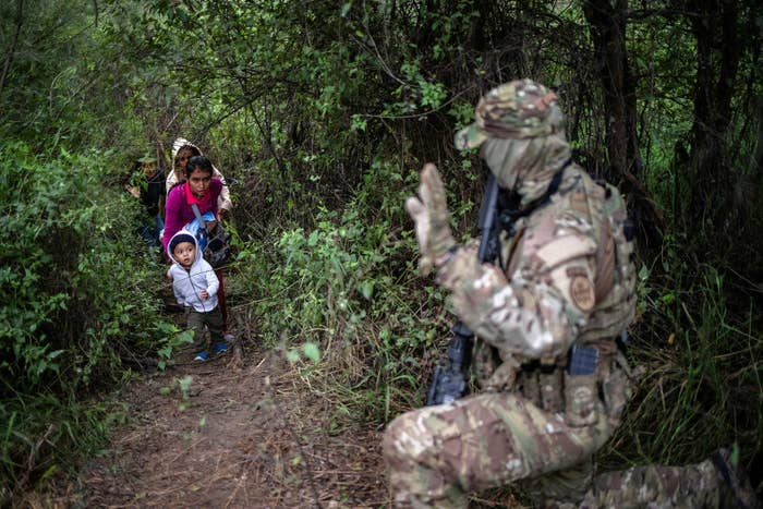 A member of the US Border Patrol Tactical Unit acknowledges family members after they illegally crossed the Rio Grande river into the United States from Mexico in Fronton, Texas, on Oct. 18.
