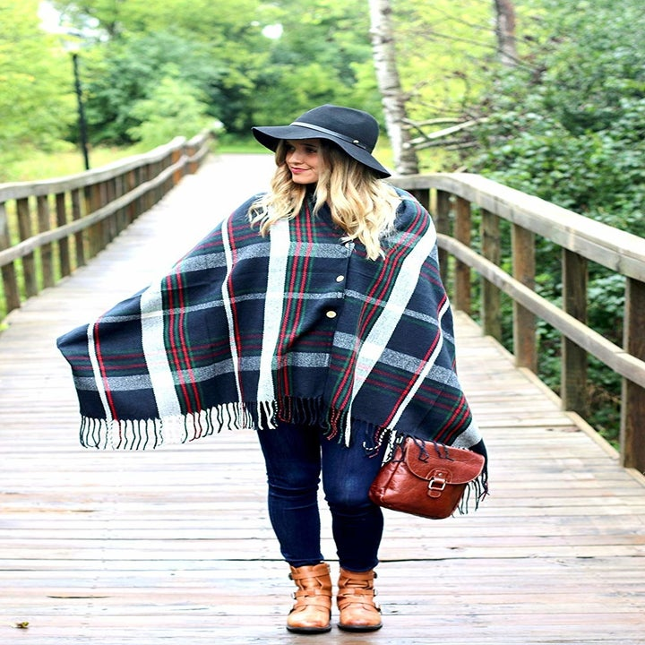 A model wearing the button front plaid shawl in navy, white, red, and green plaid