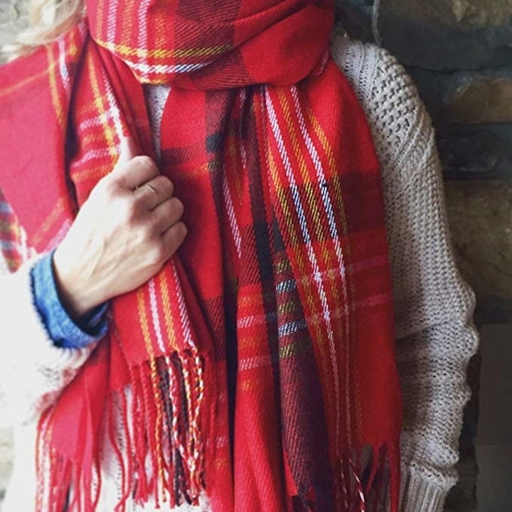 A model wearing the red plaid version as the scarf