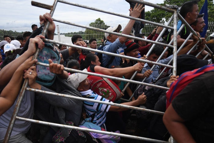 Honduran migrants in a US-bound caravan remove a barrier at the Guatemala-Mexico international border bridge.