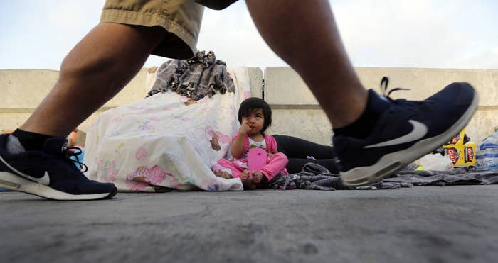 A pedestrian on the Matamoros International Bridge passes Jennifer, 2, from Guatemala, seeking asylum in the United States with her mother.