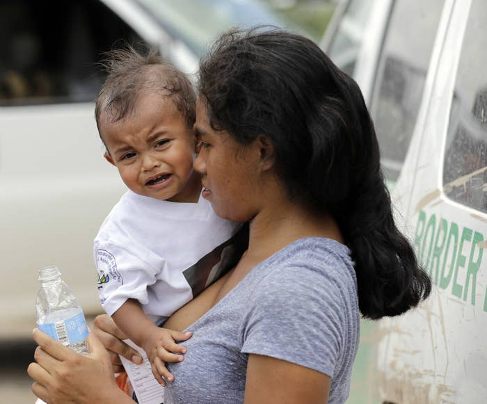 A mother immigrating from Honduras holds her 1-year-old child as they surrender to US Border Patrol agents after illegally crossing the border.