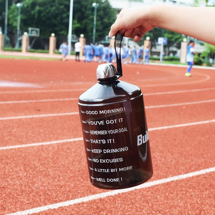 person holding giant water bottle at a track