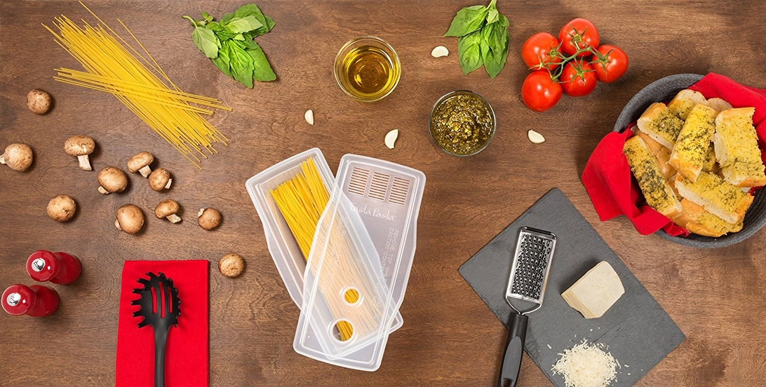 The rectangular cooker with spaghetti inside, plus the lid with strainer and two measuring holes for pasta