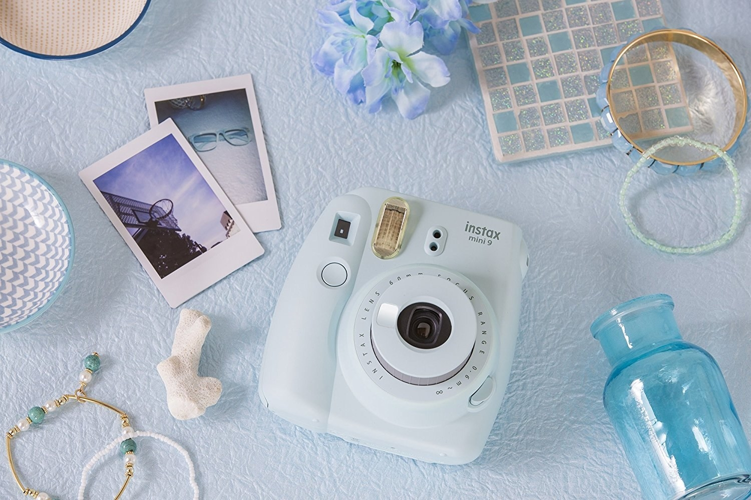 The camera in light blue, with rectangular instant photos