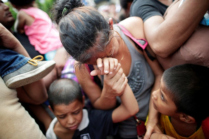 A Honduran migrant and her children after clashes at a border checkpoint to cross into Mexico, in Tecún Umán, Guatemala, on Oct. 19.