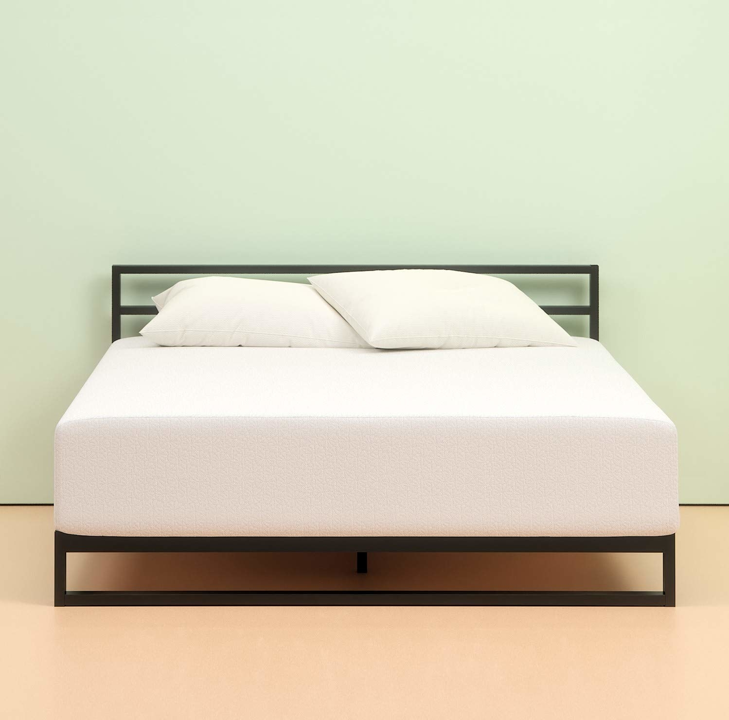 Plush mattress uncovered on metal bed frame
