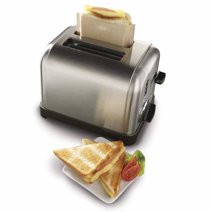 A grilled cheese sandwich, and a toaster with another grilled cheese in the bag