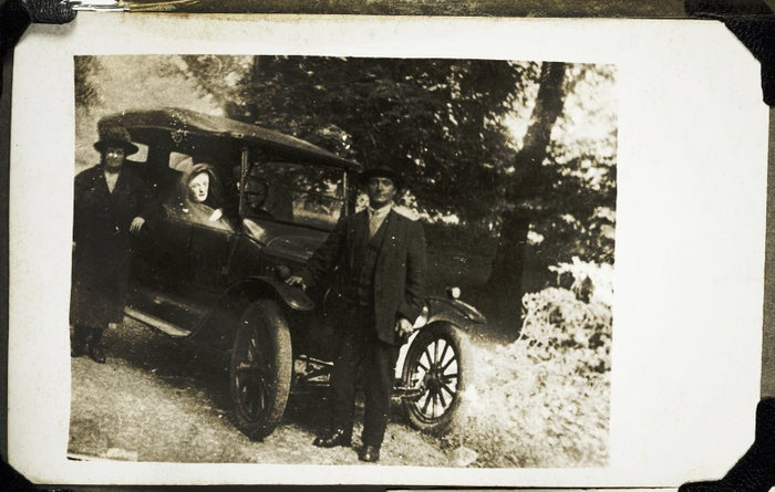 Two of William Hope's friends are seen with a figure, the couple's deceased son, at the wheel, circa 1920.