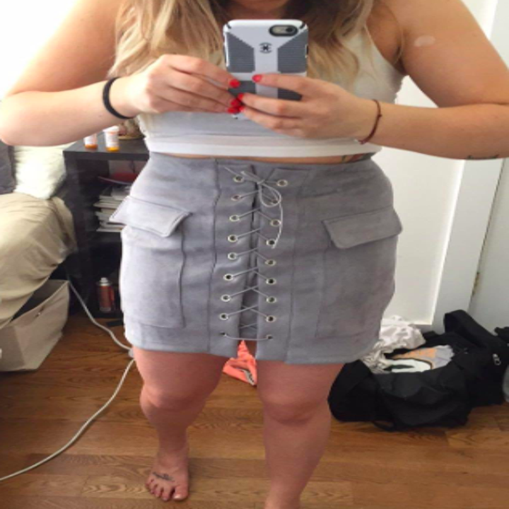 A reviewer wearing the skirt with flap pockets in gray