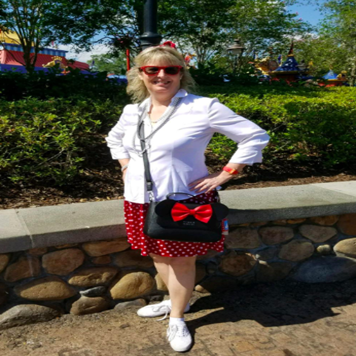 A reviewer wearing the black bag with ears and a red bow as a crossbody