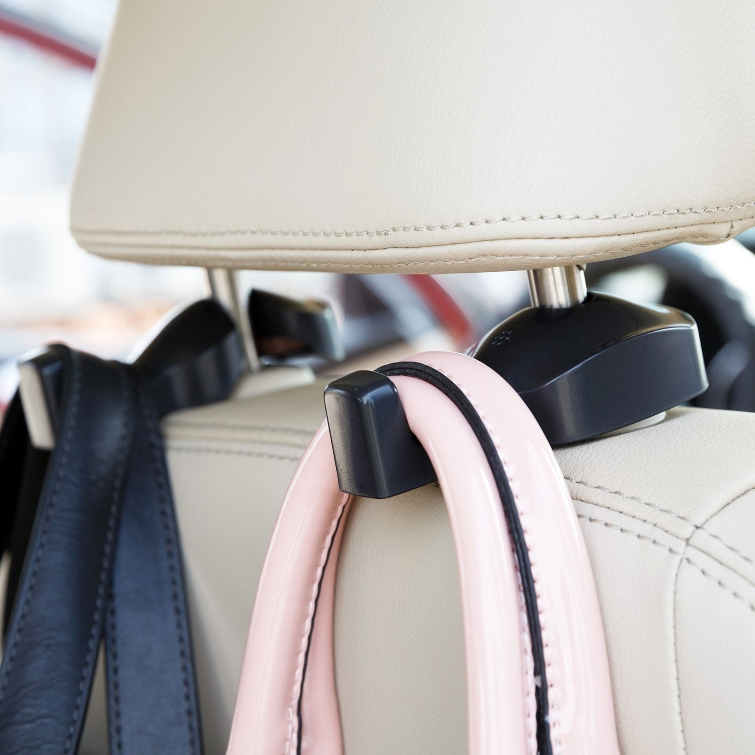A close of the hanger hooks holding bags while placed on a car's headrest.