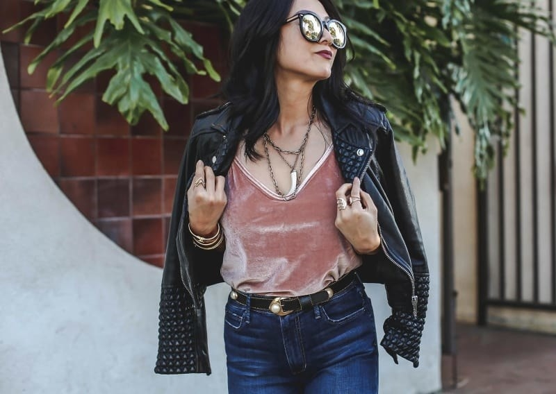 Reviewer wearing the v-neck tank top in velvet pink with a leather jacket draped over their shoulders