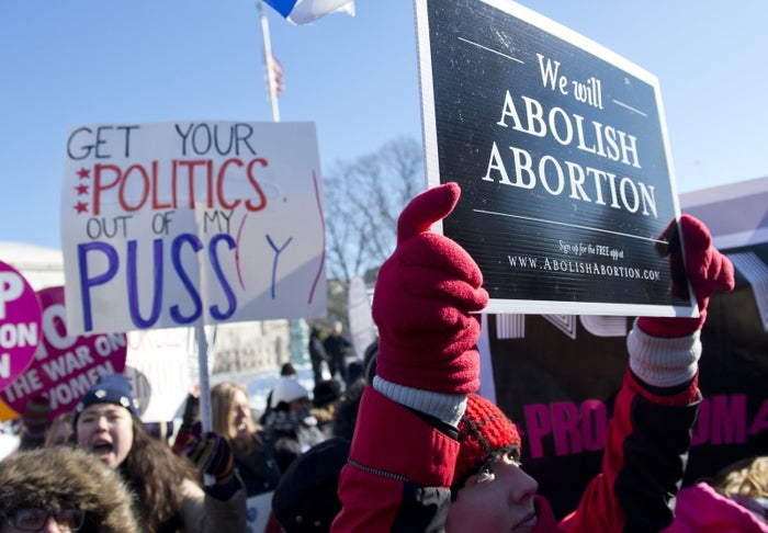 Anti-abortion demonstrators and pro-choice demonstrators hold signs as they protest in front of the US Supreme Court.