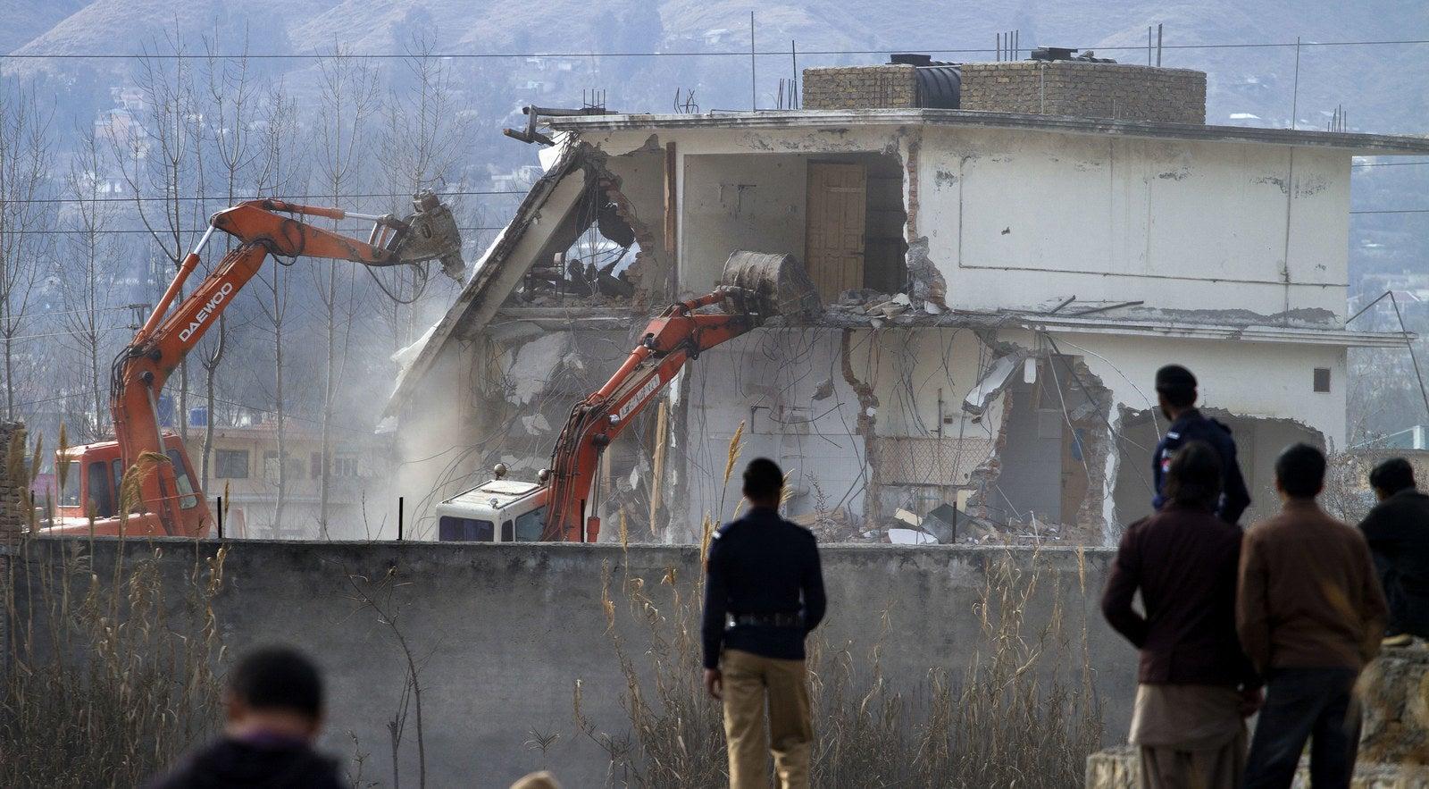 Pakistani authorities use heavy machinery to demolish the compound of Osama bin Laden in Abbottabad, Pakistan.