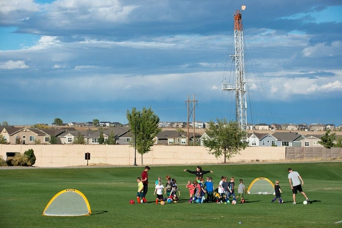 Kids playing on a field located near oil and gas infrastructure in Colorado.