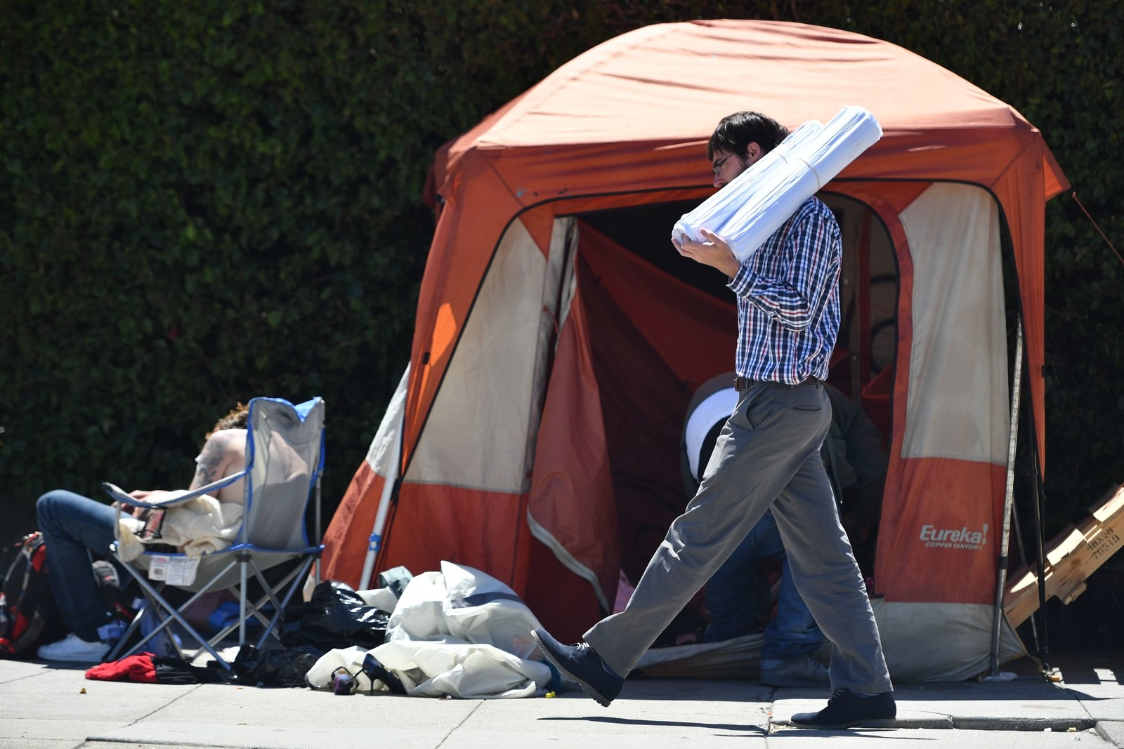 A man carrying blueprints passes a homeless encampment in downtown San Francisco.