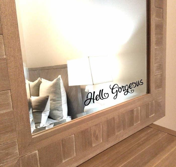 "Black sticker that says ""Hello Gorgeous"" in cursive on a mirror"