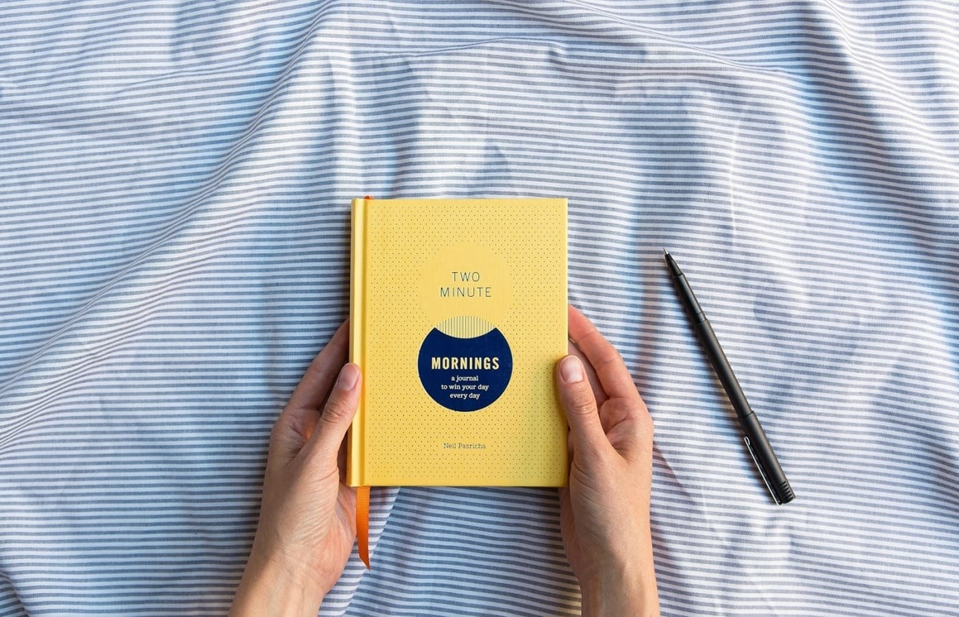 Hands holding the small yellow book