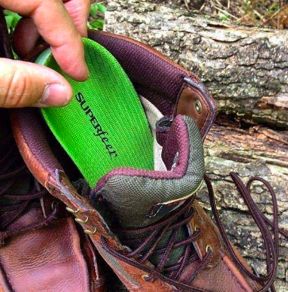 A review image of an insole being taken out of a worn hiking boot, the insole is new and already clearly formed to the owner's foot