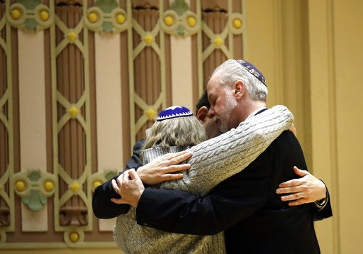 Rabbi Jeffrey Myers hugs congregants during a meeting after the shooting.