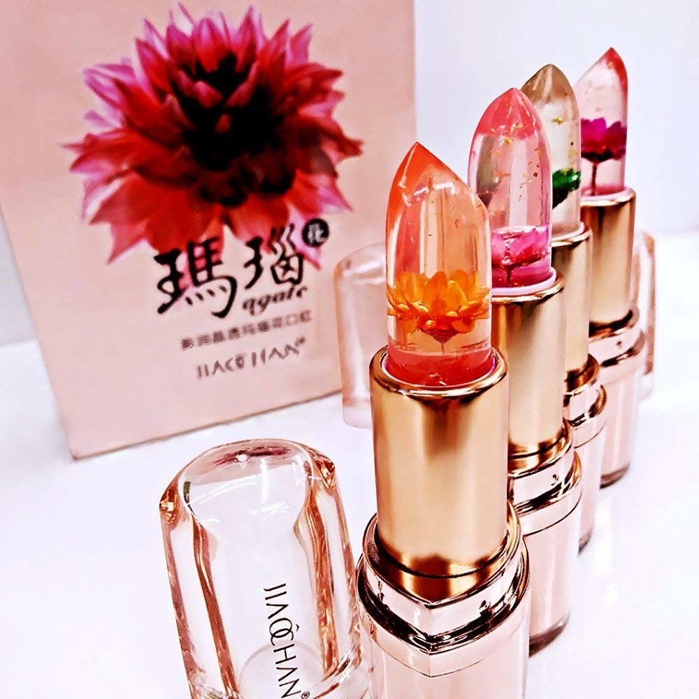 four of the rose gold lip balms with clear lipstick and flowers in the inside of it