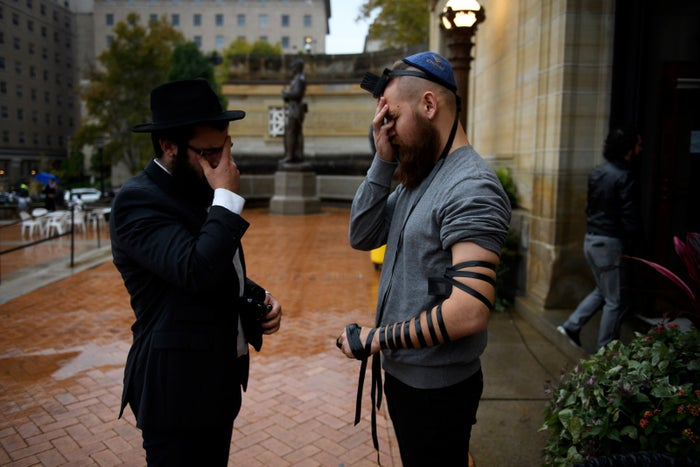 Men pray outside the Soldiers and Sailors Memorial Hall before a service to honor and mourn the victims of Saturday's mass shooting at the Tree of Life synagogue on Oct. 28 in Pittsburgh.