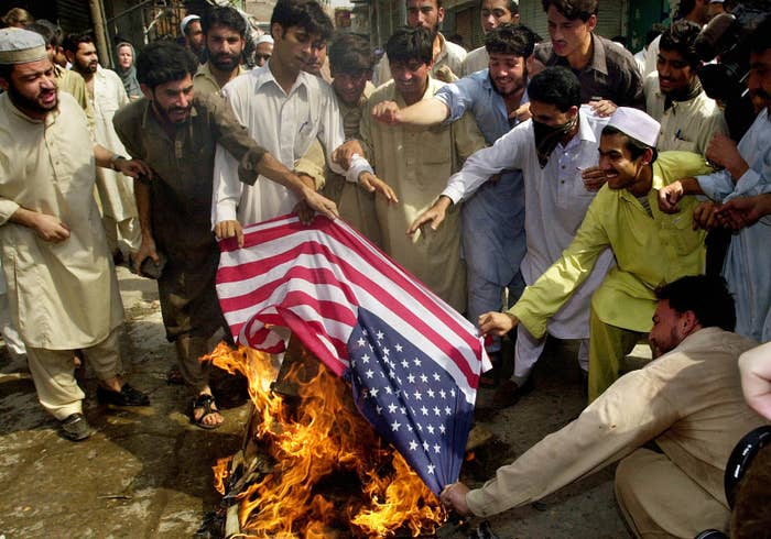 Protesters burn an American flag outside of the Madani Darul Uloom mosque on Oct. 8, 2001, in Peshawar, Pakistan, near the border of Afghanistan.