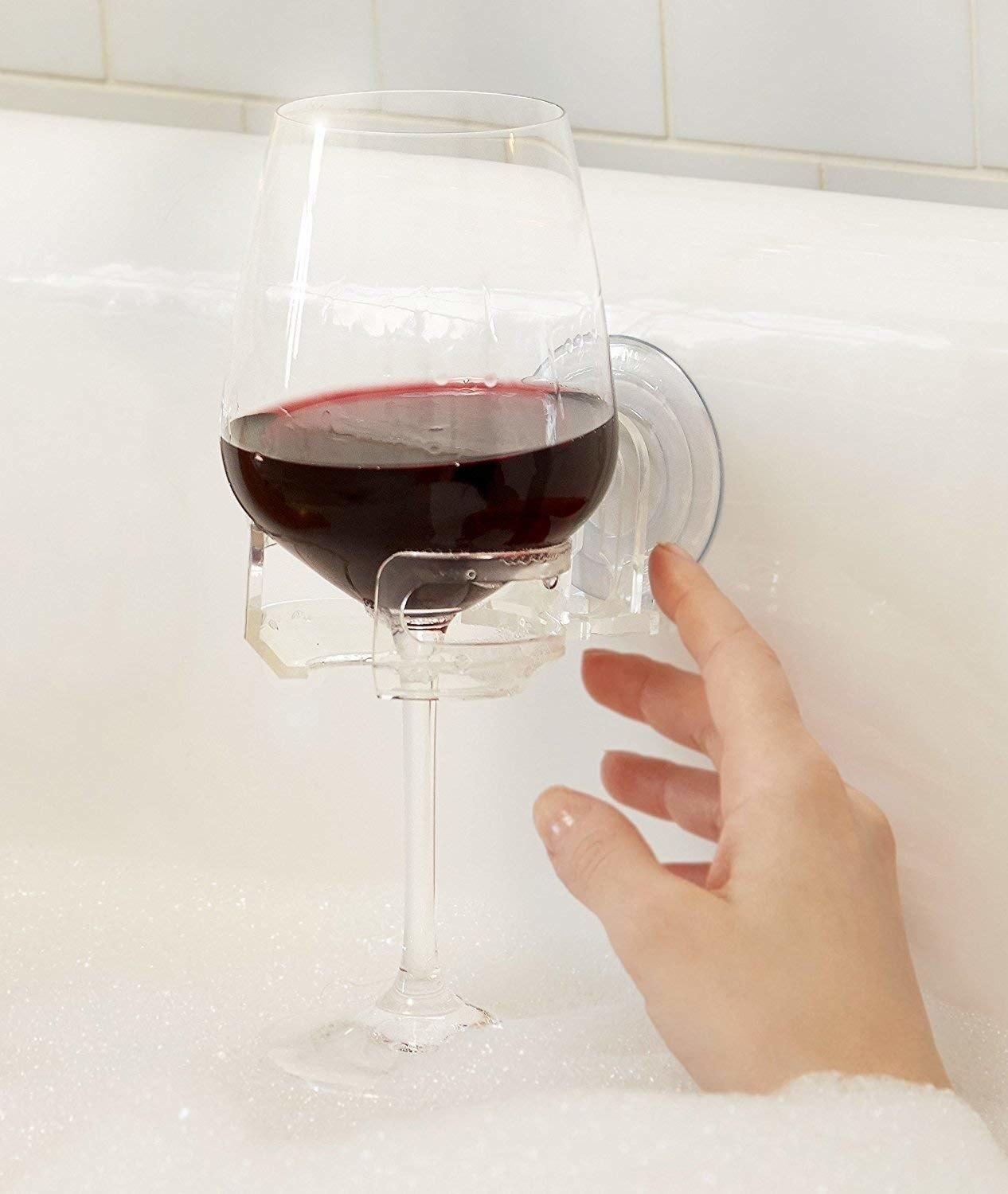 Tthe clear holder suctioned to the side of the tub with a glass of red wine in it and a hand reaching for it