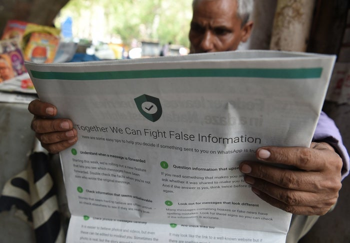 An Indian newspaper vendor reads a newspaper with a full-page advertisement from WhatsApp intended to counter fake information.