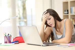 Frustrated woman at her desk, holding her head and looking at a laptop
