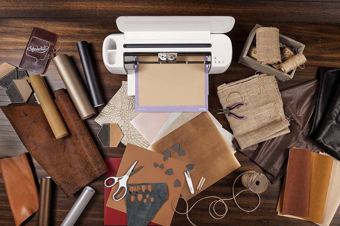A Cricut Maker on a table covered in vinyl fabric, leather, burlap, twine, and paper goods