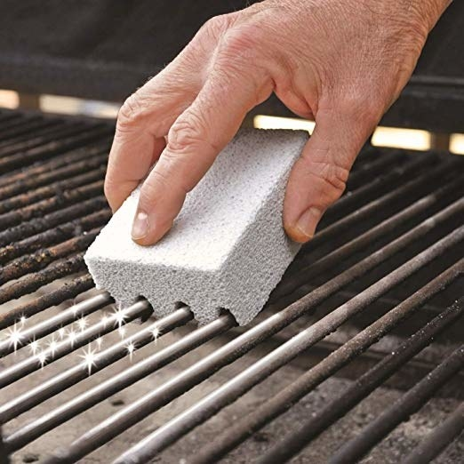 Model using the Better Grillin' scrubbing stone on grill to clean