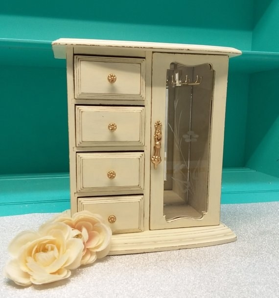 A white jewelry box with drawers on one side and a glass door on the other to hang necklaces and bracelets on