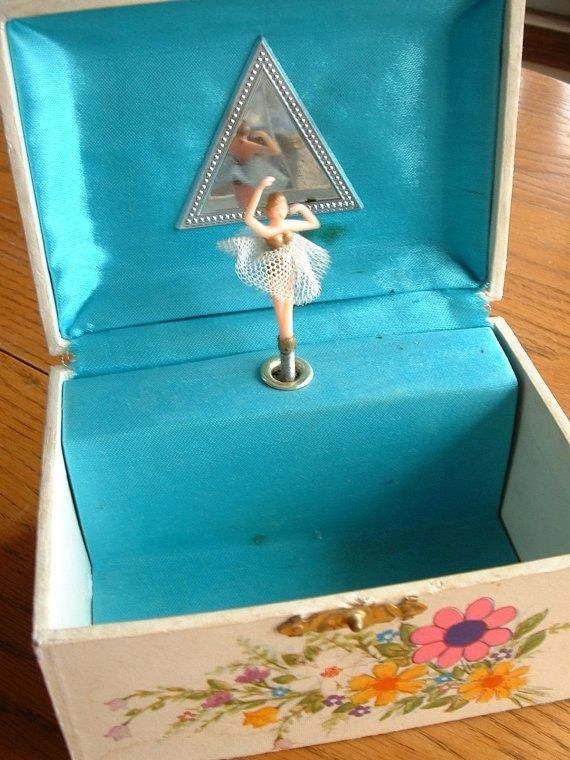 An open jewelry box with a flower pattern on the outside and with teal cloth interior and a tiny ballerina in front of mirror