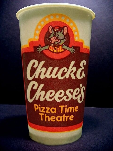 An orange and brown Chuck E. Cheese cup from the '80s with Chuck E. Cheese's Pizza Time Theatre written on it