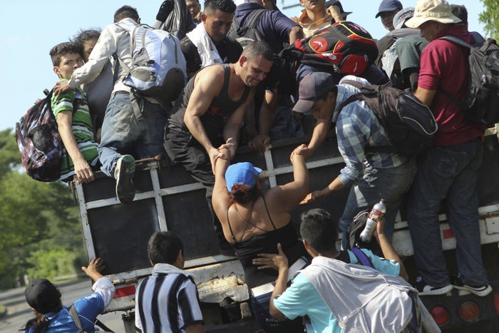 Migrants from El Salvador board a truck as they start on their way from San Salvador to the United States, on Oct. 31.