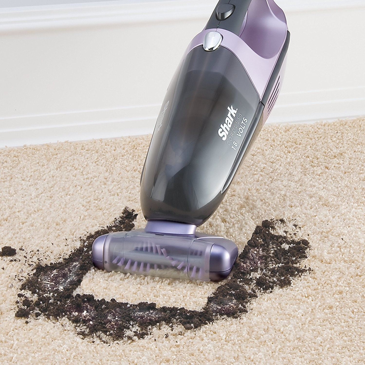 The Shark vacuum sucking up dirt from a carpeted floor