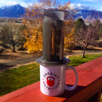 reviewer pic of the aeropress sitting on a coffee mug with the mountains in the background