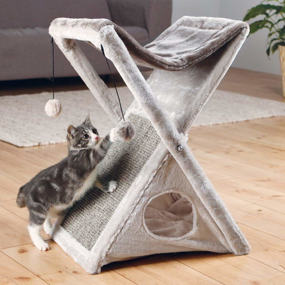 The cross-style cat toy with a hammock on top, hole in the front with an enclosed center, two balls handing from one side, and a scratching area on the side