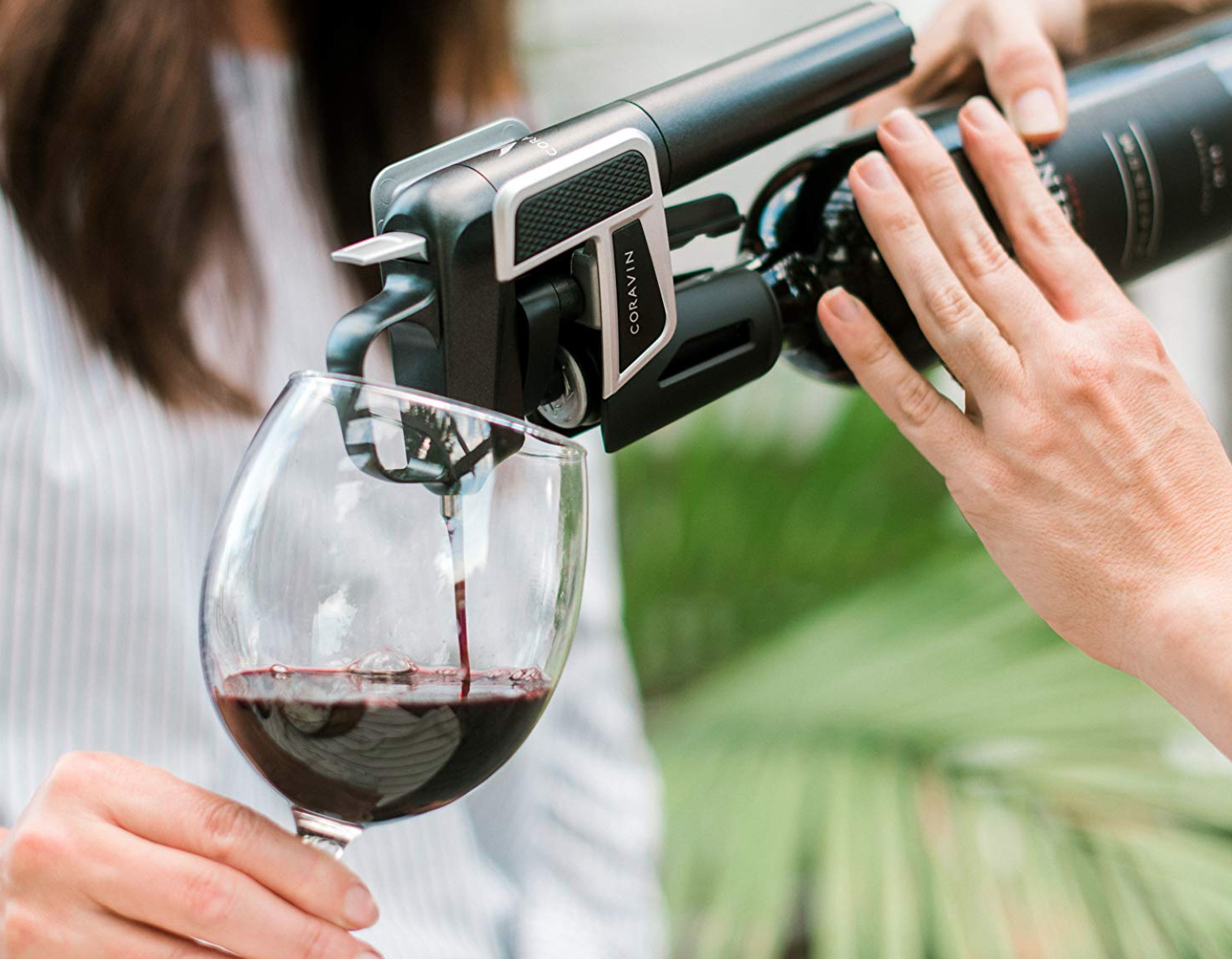 A person's hand using the Coravin wine system to pour wine into another person's wine glass