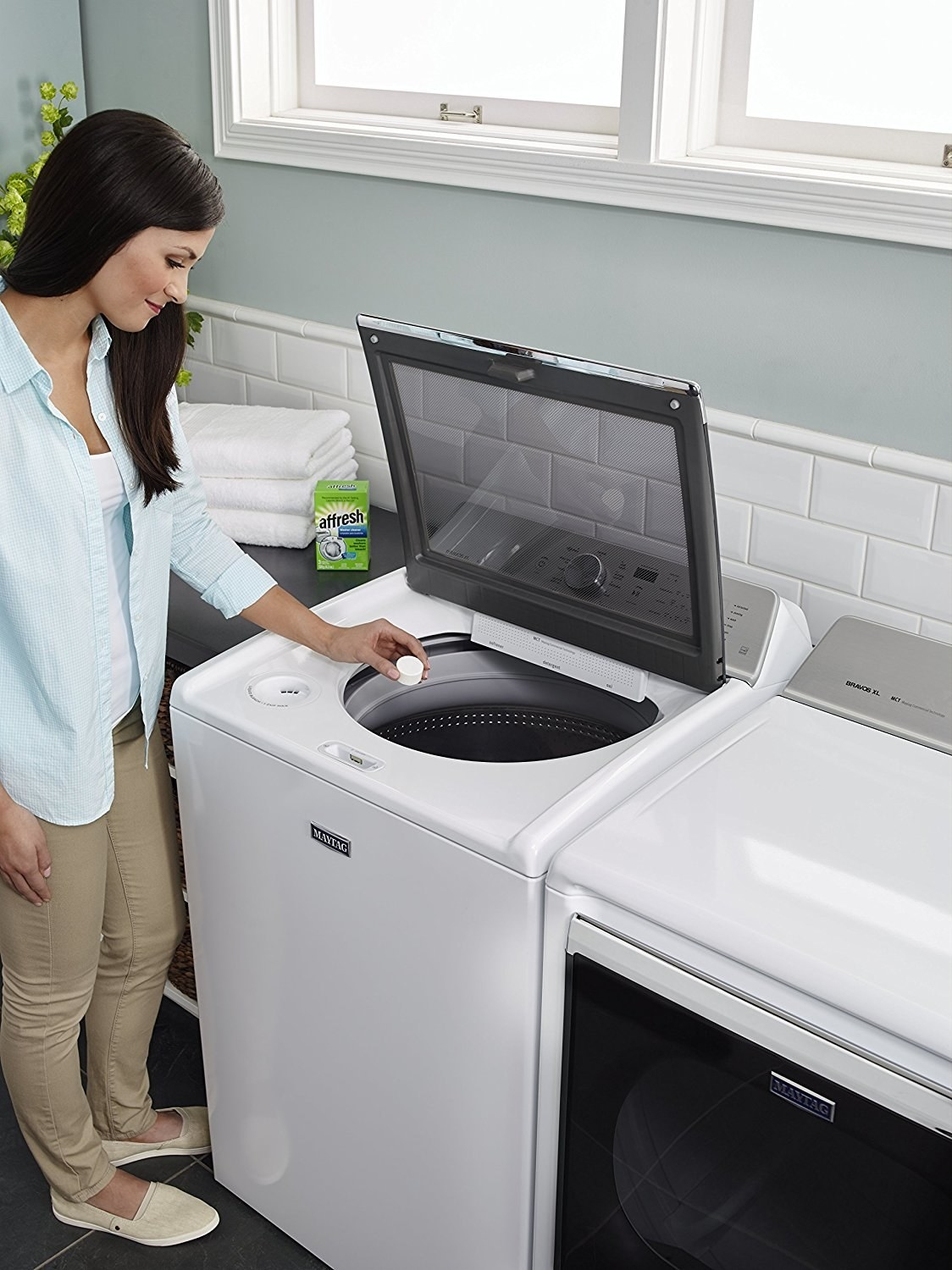 model putting white cleaning tablet into a top loading clothes washing machine